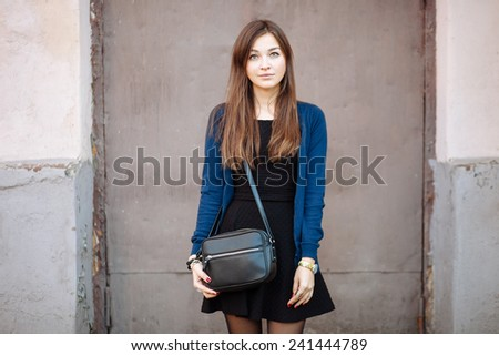 Outdoors portrait of a young cute woman with long hair against a wall - stock photo