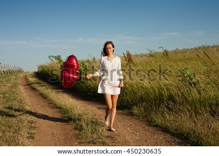 Outdoors portrait of a young woman with heart shaped balloons.