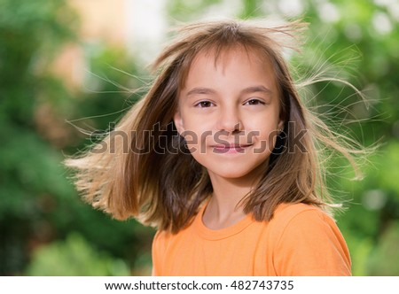 Outdoors portrait of beautiful happy girl with flying hair