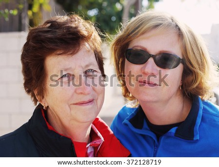 Outdoors portrait of beautiful senior woman and her adult daughter - stock photo