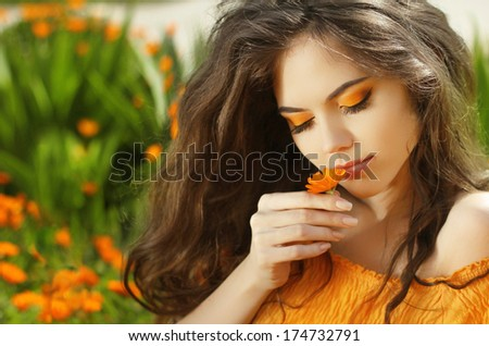 Outdoors portrait of Beautiful Teen girl smelling flower, over marigold flowers field - stock photo