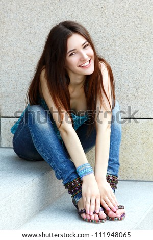 Outdoors portrait of beautiful young brunette girl sitting on stairs and smiling - stock photo