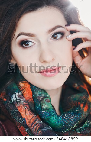 Outdoors portrait of beautiful young brunette woman, Portrait close up of young beautiful woman, lifestyle fashion scarf, beautiful expressive makeup - stock photo