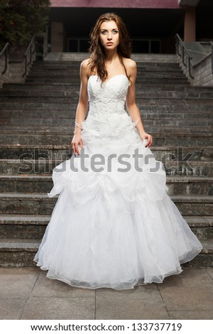 outdoors portrait of beautiful young caucasian brunette woman in white wedding dress over gray stairs on background - stock photo