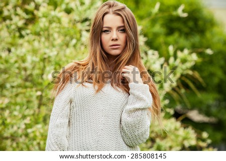 Outdoors portrait of beautiful young girl in casual white sweater.