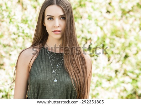 Outdoors portrait of beautiful young woman in casual green dress posing in summer garden.  - stock photo