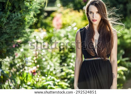 Outdoors portrait of beautiful young woman in luxury black dress posing in summer garden.  - stock photo