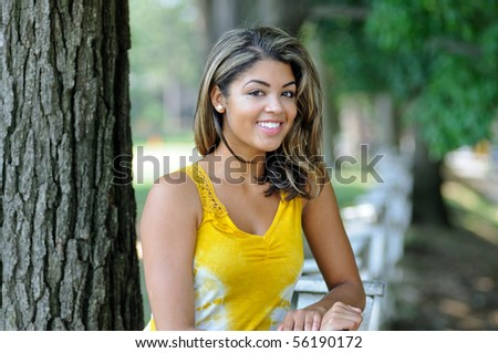 Outdoors portrait of beautiful young woman in yellow summery blouse
