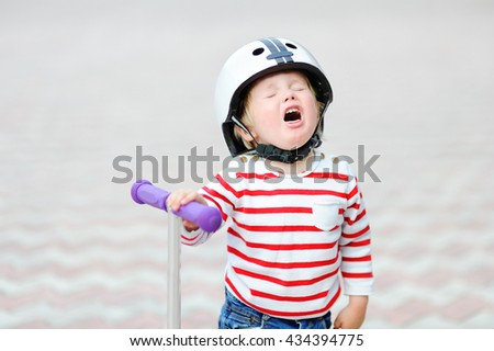 Outdoors portrait of crying toddler boy in safety helmet with scooter  - stock photo