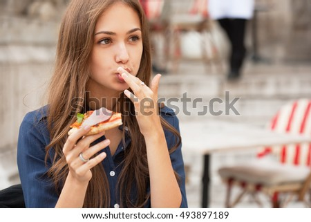 Outdoors portrait of gorgeous young woman having delicious pizza.