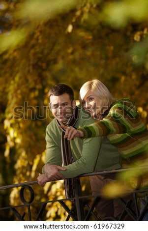 Outdoors portrait of happy couple standing in autumn park, woman showing something to man, smiling.? - stock photo