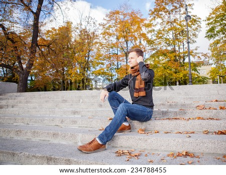 Outdoors portrait of happy young man in autumn park