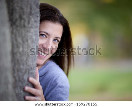 Outdoors portrait of happy young woman leaning to tree trunk in autumn forest - stock photo