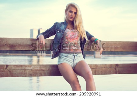 Outdoors portrait of romantic fashion young woman with long legs and hair in summer casual clothes standing on pier near river. Urban lifestyle. Photo toned warm colors