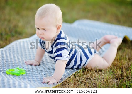 Outdoors portrait of six month old baby play with bright toy  - stock photo