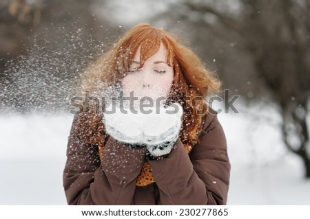 Outdoors portrait of young beautiful woman having fun in winter  - stock photo