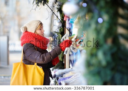 Outdoors portrait of young beautiful woman on a Christmas market - stock photo