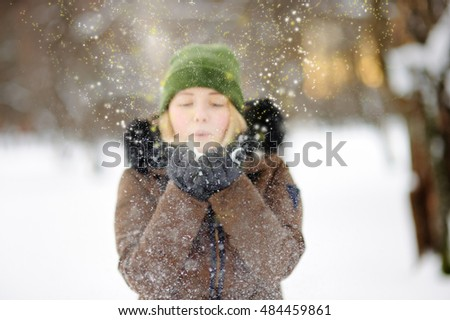 Outdoors portrait of young beautiful woman playing with. Winter mystery