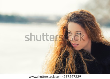 Outdoors portrait of young cheerful beautiful woman having fun in winter spring. Positive face expression  - stock photo