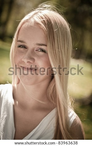 Outdoors portrait of young smiling woman (teenager) - warm tone - stock photo