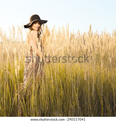 Outdoors shot of a beautiful young model in tallgrass - stock photo