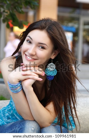 Outdoors street portrait of beautiful young brunette girl - stock photo