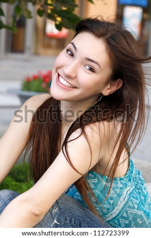 Outdoors street portrait of beautiful young brunette teen girl - stock photo