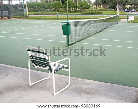 Outdoors tennis court on a sunny day, with a chair in the foreground. - stock photo