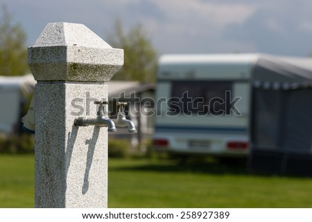 Outdoors water tap at camping site on a sunny day. Blurry caravan in the background. - stock photo
