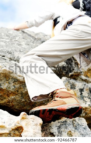 outdoors woman climbs a rock while hiking and exploring - stock photo