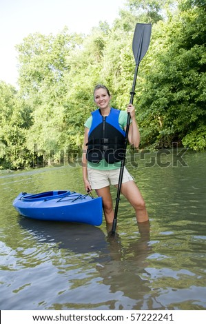 Outdoorsy active female wearing a life jacket and holding a paddle and a kayak