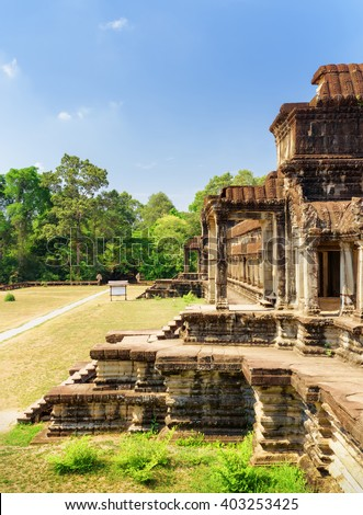 Outer hallway with columns at east side of ancient temple complex Angkor Wat in Siem Reap, Cambodia. Blue sky and woods in background. Mysterious Angkor Wat is a popular tourist attraction. - stock photo