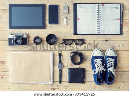 Outfit of a stylish traveler or a freelance journalist. Set of different objects and equipment: tablet, phone, album, glasses, camera, lenses, wallet, gumshoes, usb storage and watches. - stock photo