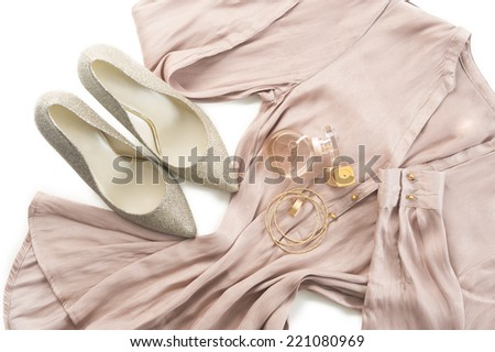 Outfit of stylish ladies clothing on a white background with elegant silver court shoes, gold bangles and a perfume bottle on a neutral tone dress or tunic for smart casual wear or evening wear - stock photo