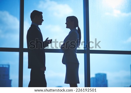 Outlines of business partners talking by the window in office - stock photo