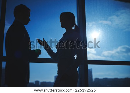Outlines of businessman and businesswoman communicating by the window - stock photo