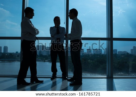 Outlines of three businessmen communicating in office - stock photo