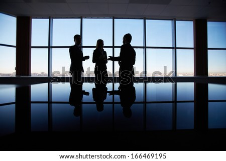 Outlines of three office workers interacting by the window - stock photo