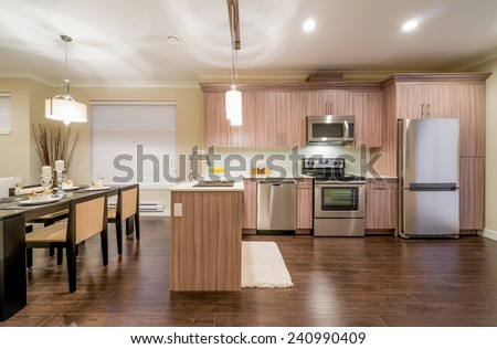 Outlook at the luxury modern living suite : kitchen and nicely decorated dining table.  Interior design. - stock photo