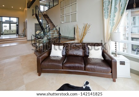 Outlook at the luxury spacious modern living room with the leather sofa, coach at the front and stairs to the upper level. Interior design.
