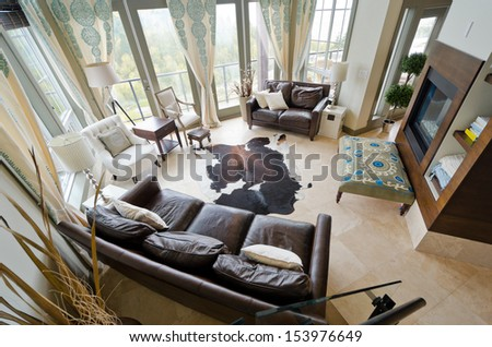 Outlook from above at the luxury spacious modern living room with the fireplace and some leather coaches. Interior design. - stock photo