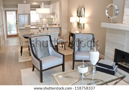 Outlook of the luxury living suite : dining room and the kitchen at the back with two modern leather chairs in front of