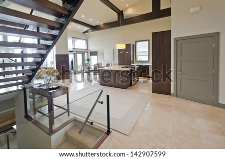Outlook, panorama at the luxury modern living space with the kitchen, dining room and stairs to the upper level and to the basement. Interior design. - stock photo