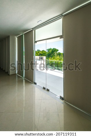 Outlook, view from inside through the glass doors to the modern glass and steel balcony, deck, patio, promenade railing. Exterior, interior design. Vertical. - stock photo
