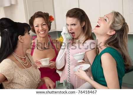 Outraged woman on phone with three friends in a kitchen - stock photo