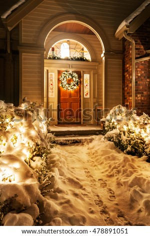 Outside Christmas lights line path to a front door on a snowy winter night