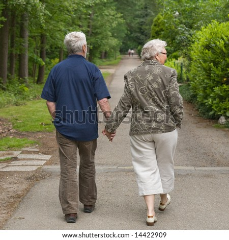 outside portrait of an elderly couple walking along a forest road