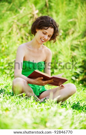 outside portrait of beautiful curly girl sits on grass and reading book in park - stock photo