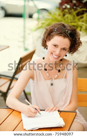 outside portrait of beautiful curly young woman sitting at the park cafe table and white pen in writing-book - stock photo