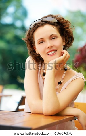 outside portrait of beautiful happy girl sitting at the park cafe table - stock photo